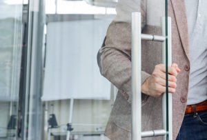 Employment consultant holding onto recruitment office door